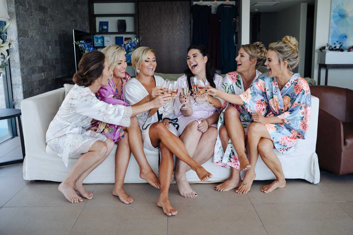 Bridesmaids getting ready on the wedding day sharing a glass of sparkling wine