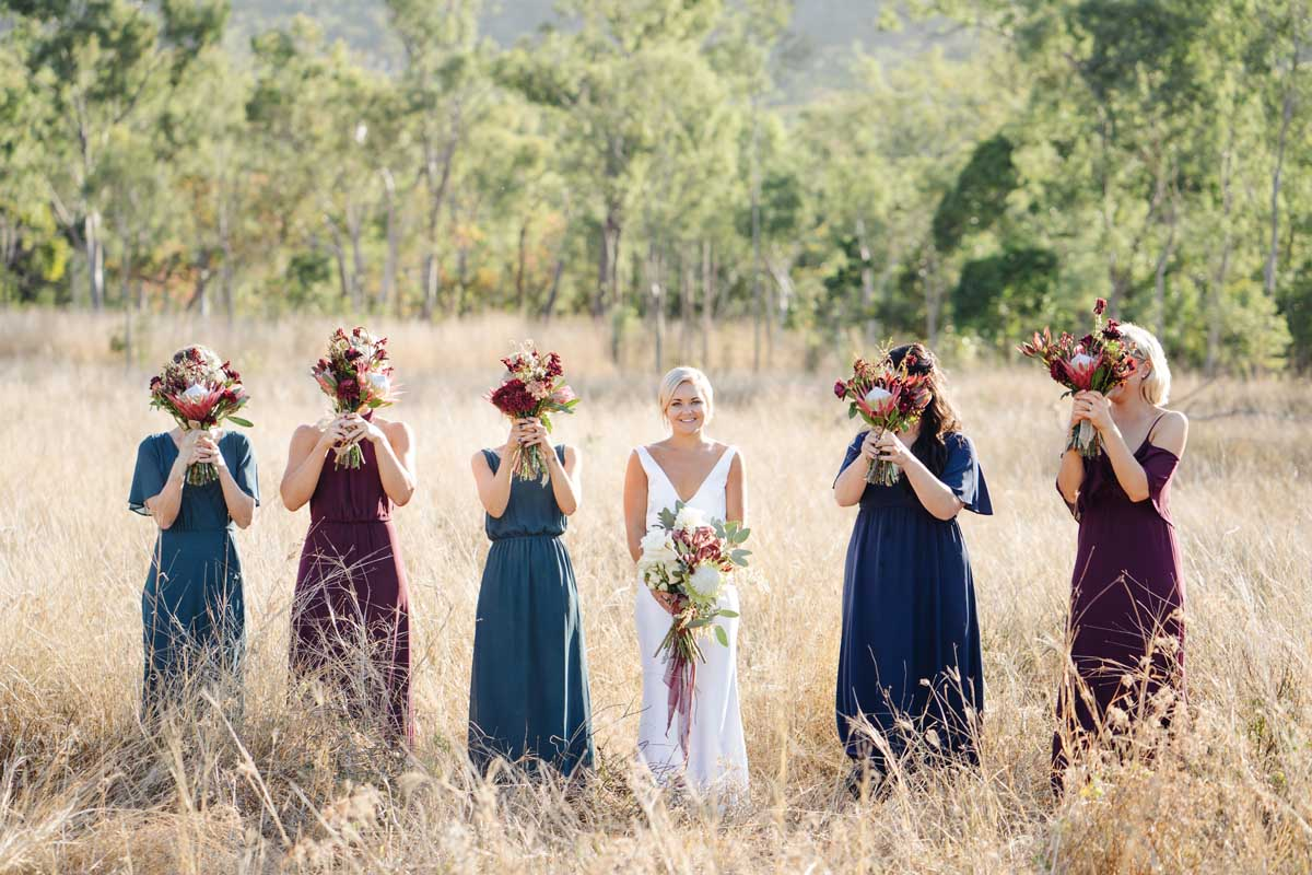 Cheeky bridesmaid photo with flowers in front of their faces