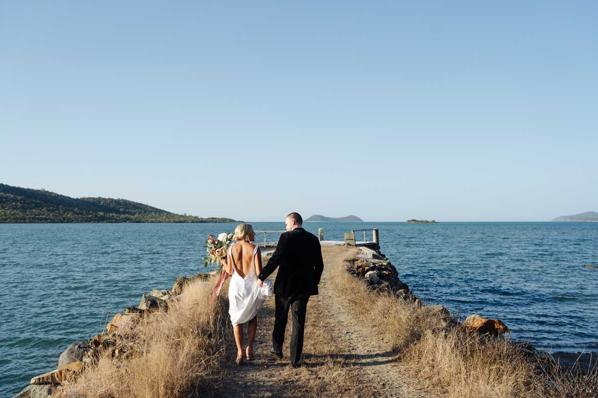 Bride and groom casually walking along a rustic jetty