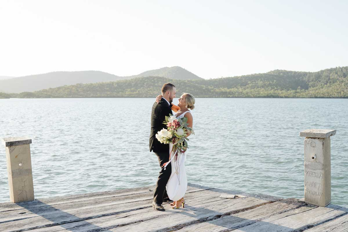 Bride and groom looking at each other standing on a jetty with the ocean and rolling hills in the background