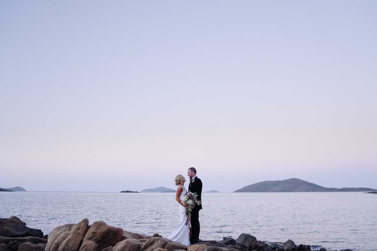 Bride and groom on rocks by the beach at sunset at Earlando