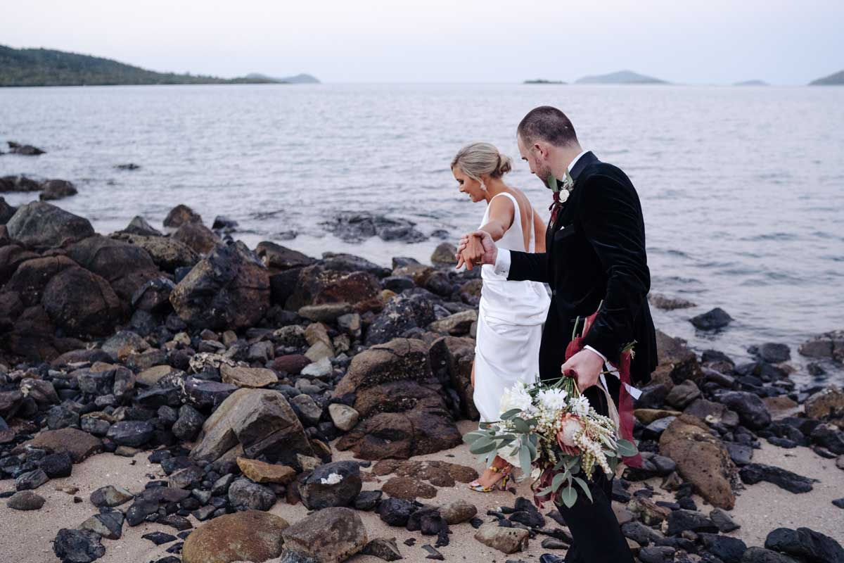 Groom helping bride walk along the beach and rocks at sunset
