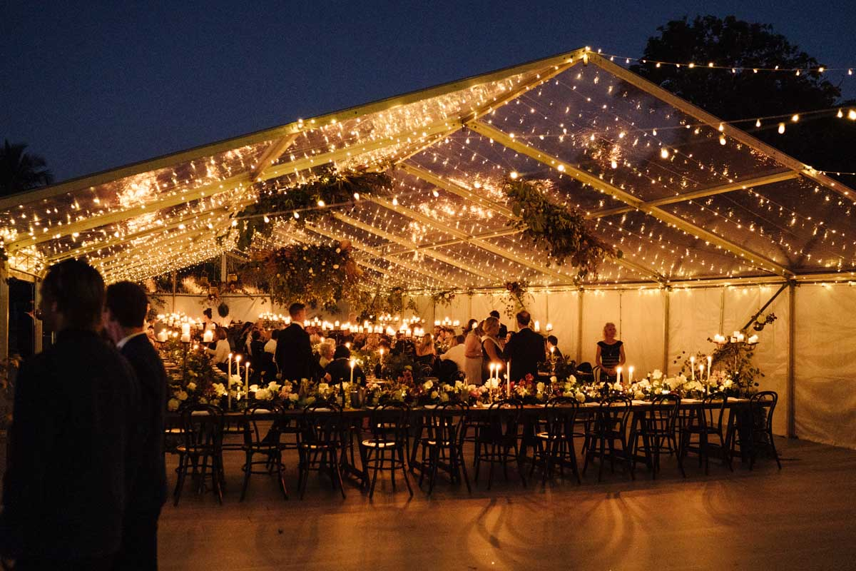 Clear marquee with fairy lights and candles at night