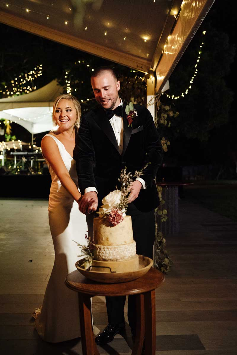Bride and groom cutting the wedding cheese wheel cake
