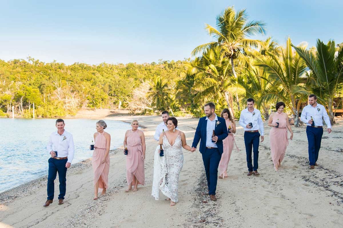 Bridal party walking on the beach at Earlando