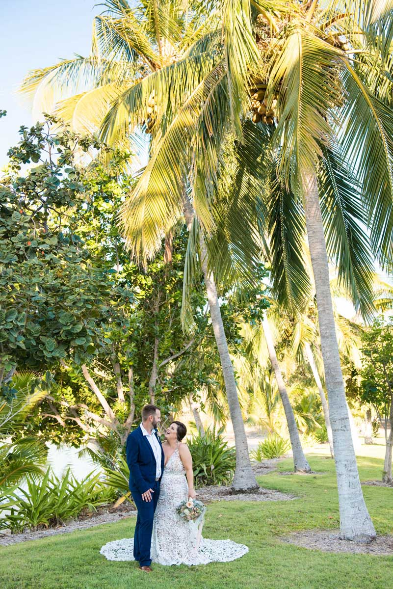 Bride and groom under the palm trees at Earlando Whitsundays