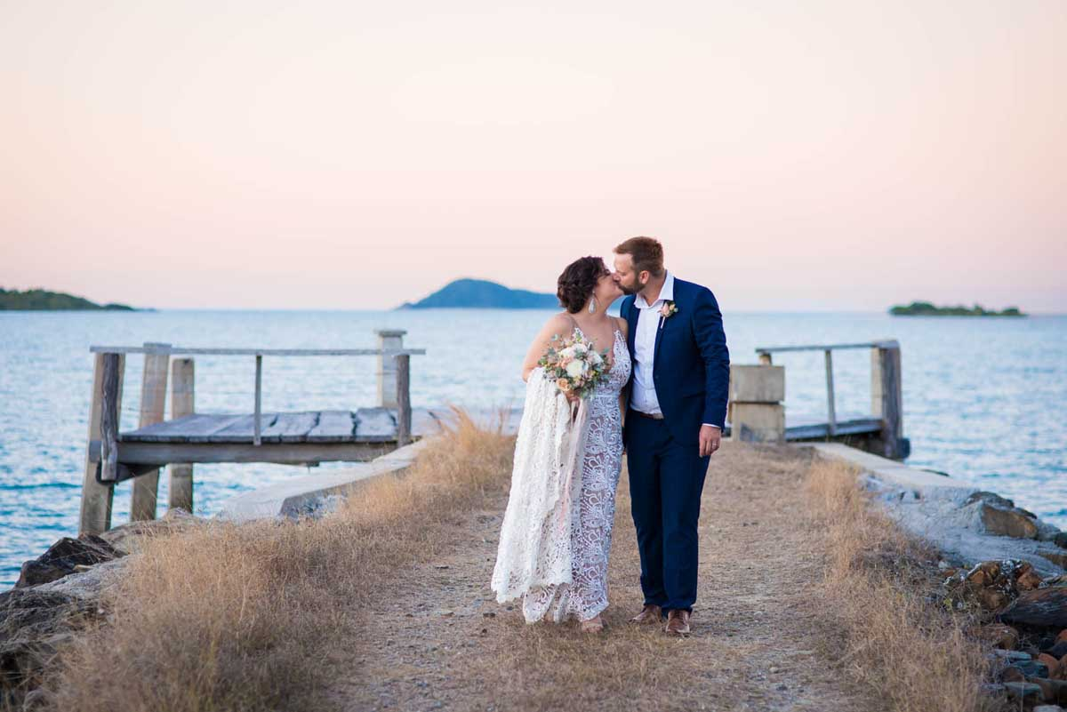 Bride and groom at sunset on a jetty share a kiss
